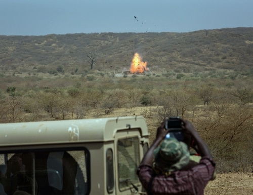 In this photo taken on Thursday, Feb. 18, 2016, a participant, foreground, takes photos as an car explodes during U.S-led Flintlock military training in Thies, Senegal. The training for 50 Senegalese police, gendarmes, customs and judicial officials is part of the annual U.S.-led Flintlock exercises, a more than decade-old effort to help Africans counter threats from extremist militants. Held in Senegal and Mauritania, this year is the first time they are involving law enforcement in such training designed to improve intelligence-gathering and cross-border communication as well as bridge gaps between military and first responders. More than 1,700 military and law enforcement personnel from about 30 countries are participating in the month-long exercise. (AP Photo/Vincent Tremeau)