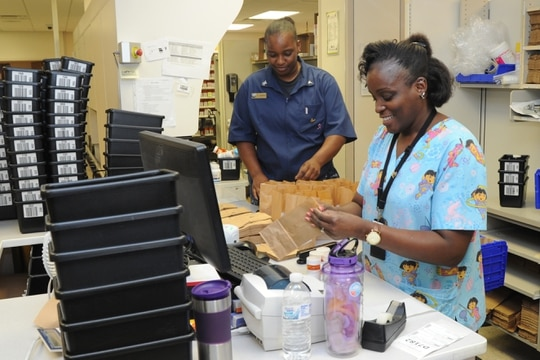 Pharmacy costs will remain flat for Tricare patients in 2021. Here, Wanda Ward, a pharmacy tech at Naval Hospital Pensacola, fills a prescription for TRICARE beneficiaries June 11, 2019. (Jason Bortz/Navy)