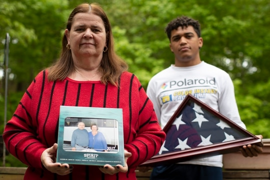 In this May 22, 2020, photo Florence Hopp, left, holds a photograph of herself and her husband Robert Hopp during a cruise in 2017, as her son J.J. Brania-Hopp holds the American flag the military presented to them after his father's death at their home in Boonton, N.J. Hopp was one of at least 79 residents of a veterans home in Paramus, New Jersey, to die from COVID-19, making the state-run facility one of the nation's worst hot spots for the virus. (Mary Altaffer/AP)
