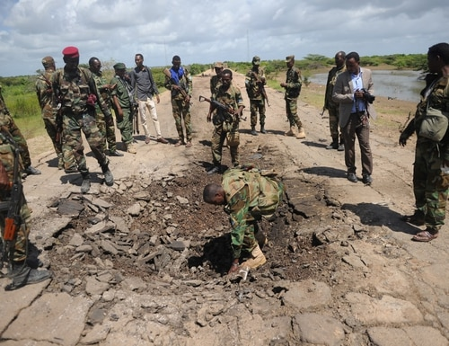 Somali soldiers look at a blast mark of car bomb attack at a check point near Sanguuni military base, where an American special operations soldier was killed by a mortar attack on June 8, about 450 km south of Mogadishu, Somalia, on June 13, 2018. (Mohamed Abdiwahab/AFP via Getty Images)