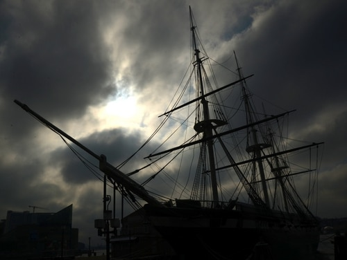 The sun breaks through the morning gloom to illuminate the USS Constellation at dock on the Baltimore Harbor during a Defense Information School photojournalism exercise March 4, 2016, Baltimore, MD.