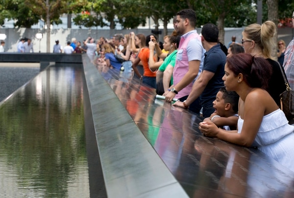 In this Sept. 9, 2015, file photo, visitors look at the waterfalls at the World Trade Center Memorial in New York. (Mark Lennihan/AP)