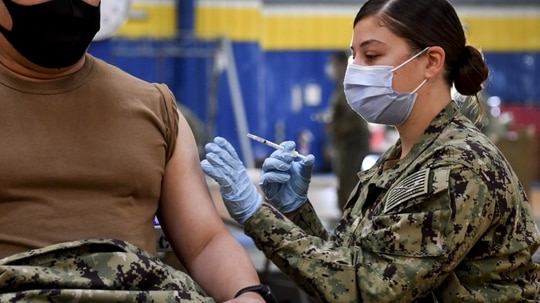 Hospital Corpsman 2nd Class Angelina Mangram, assigned to Fleet Surgical Team 3, administers the COVID-19 vaccine to a sailor at the Naval Base San Diego fitness center Jan. 6. (MC1 Julio Rivera/Navy)