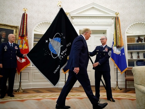 Chief of Space Operations at United States Space Force Gen. John Raymond, left, and Chief Master Sgt. Roger Towberman, right, hold the U.S. Space Force flag as President Donald Trump walks past it, in the Oval Office of the White House in Washington on Sept. 1, 2020. (Alex Brandon/AP Photo)