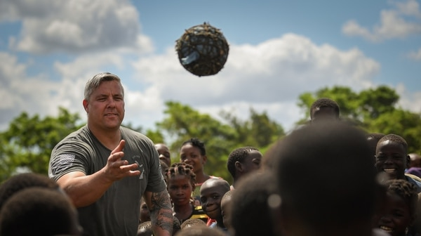 Army Maj. Eric Buendia, assigned to Combined Joint Task Force-Horn of Africa, entertains local Mozambican children in Bebedo, Mozambique, April 8. (Staff Sgt. Corban Lundborg/Air Force)