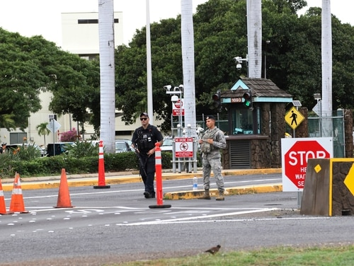 In this Dec. 4 file photo, security forces stand outside the main gate at Joint Base Pearl Harbor-Hickam in Hawaii. A live mortar round was found in a vehicle late Tuesday at a gate to the sprawling Pearl Harbor military base, shutting down the base for hours on Wednesday. (Caleb Jones/AP)