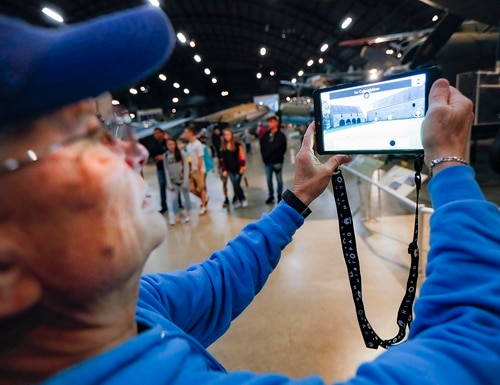 In this April 26, 2019, photo, Deane Sager, of Louisville, uses a Histopad tablet to view scenes from operations on the western front of World War II at the The National Museum of the U.S. Air Force, in Dayton, Ohio. (John Minchillo/AP)