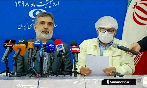 Behrouz Kamalvandi, left, spokesman for Iran's atomic energy agency, listens to a man wearing a surgical mask, who was introduced by the newsreader only as an official with the Ahmadi Roshan nuclear site in Natanz, Iran, during a news conference. (IRIB News Agency via AP)