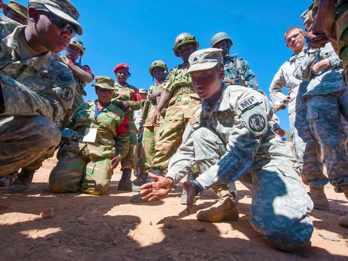 U.S. Army Sgt. Tyesha Smith (right), a military policeman with the 93rd Military Police Battalion, explains a tactical movement procedure to members of the Zambian Defense Force during an exercise at Southern Accord 2015 in Lusaka, Zambia on Aug. 10. The annual exercise provides U.S. military, United Nations allies and the Zambian Defense Force an opportunity to work and train together as a joint, combined peacekeeping allied force. (U.S. Army Africa photo by U.S. Air Force Staff Sgt. Brian Kimball)