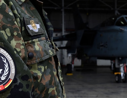 A soldier of the German Armed Forces Bundeswehr wears a badge of the combat wing (Einsatzgeschwader) Counter DAESH Incirlik next to a German Tornado jet in a hangar before a statement of the German and Turkish defence ministers at the air base in Incirlik, Turkey, on January 21, 2016. / AFP / POOL / TOBIAS SCHWARZ (Photo credit should read TOBIAS SCHWARZ/AFP/Getty Images)