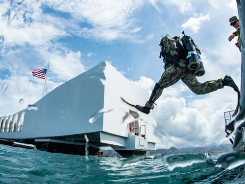 Builder 2nd Class Aaron Brown, assigned to Underwater Construction Team 2, enters the water for a dive on the USS Arizona Memorial at Joint Base Pearl Harbor-Hickam during the Rim of the Pacific exercise on July 13, 2018. (MC1 Arthurgwain L. Marquez/U.S. Navy)