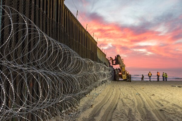 U.S. Border Patrol agents at Border Field State Park in San Diego watch over personnel reinforcing the border fence with concertina wire, Nov. 15, 2018. (Mani Albrecht/Customs and Border Protection)