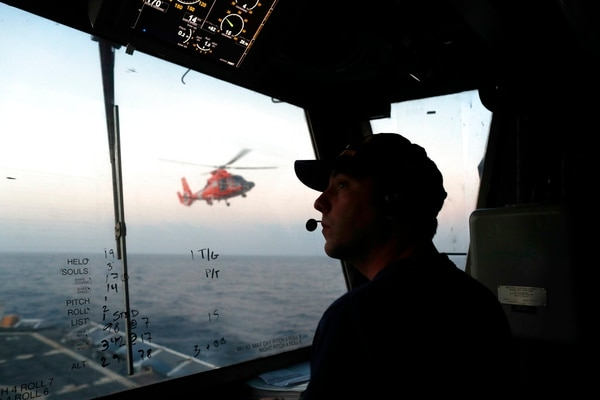 In this March 2, 2017, photo, an unidentified U.S. Coast Guardsman communicates with the pilot of a helicopter during take-off and landing exercises on the U.S. Coast Guard cutter Stratton in the eastern Pacific Ocean. (Dario Lopez-Mills/AP)