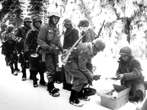 "In this Jan. 13, 1945 file photo, and provided by the U.S. Army, American soldiers of the 347th U.S. Infantry wear heavy winter gear as they receive rations in La Roche, Belgium.It was 75 years ago that Hitler launched his last desperate attack to turn the tide for Germany in World War II. It was 75 years ago that Hitler launched his last desperate attack to turn the tide for Germany in World War II. At first, German forces drove so deep through the front line in Belgium and Luxembourg that the month-long fighting came to be known as The Battle of the Bulge. When the Germans asked one American commander to surrender, the famous reply came: ""Nuts!"