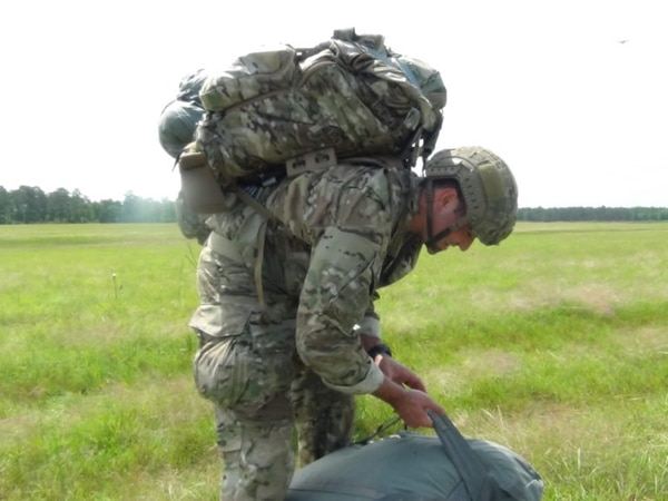 Staff Sgt. Jake Leveille, Regimental Air NCO, musters up his T-11 parachute while bearing the Mystery Ranch Patrol Pack after conducting static line airborne operations and landing on Fryar Drop Zone, Fort Benning, Georgia. (Sgt. 1st Class Ian Seymour/Army)