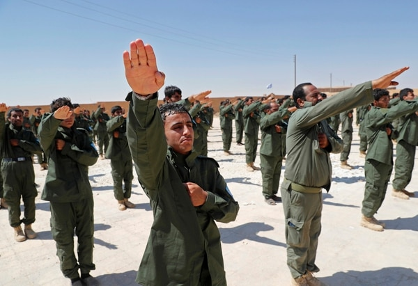 Syrian Internal Security Forces are sworn in during their graduation ceremony, at Ain Issa desert base, in Raqqa province, northeast Syria, Thursday, July 20, 2017. Some 250 residents of Syria's Raqqa province are the latest batch to graduate from a brief U.S-training course that is preparing an internal security force to hold and secure areas as they are captured from Islamic State militants. (Hussein Malla/AP)