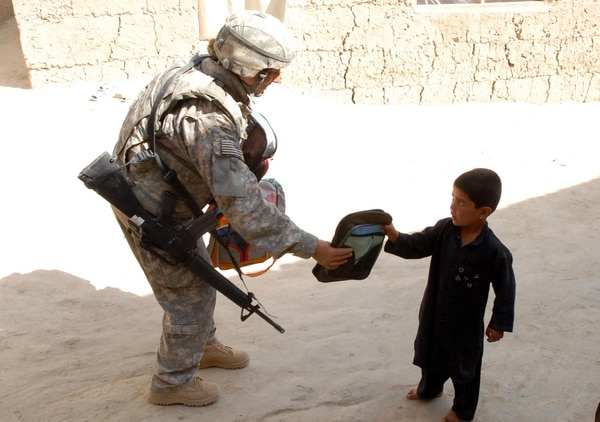 Air Force Tech Sgt. Michelle Stokes, assigned to a counter-improvised explosive device team, distributes school supplies to children in the village of Polerad, Logar province Afghanistan, in October 2009. (Pfc. Melissa Stewart/Army)