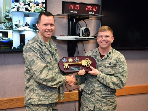 Lt. Col. Armon Lansing (right), 4th Space Operations Squadron commander, accepts a key from Col. David Ashley, Space and Missile Center AEHF program manager, during a ceremony transferring the fourth Advanced Extremely High Frequency satellite to the 4th Space Operations Squadron at Schriever Air Force Base, Colorado on May 3. (Kathryn Calvert/U.S. Air Force)