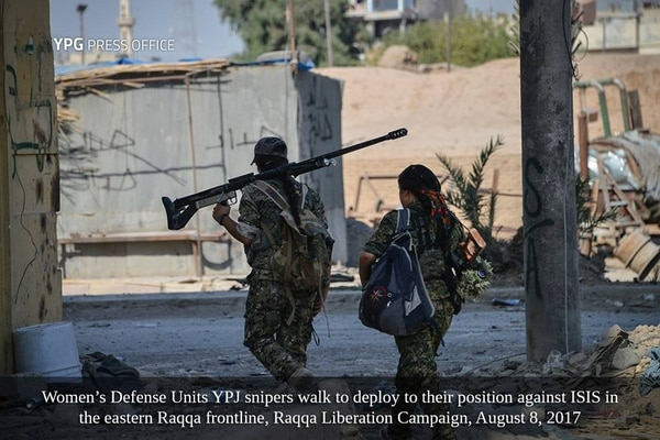 A sniper with the Women's Defense Unit, or YPJ walks to her position carrying a Zagros sniper rifle.