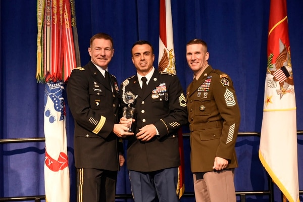 Sgt. 1st Class Sean Acosta, center, poses with his NCO of the Year Award, alongside Army Vice Chief of Staff James McConville, left, and Sergeant Major of the Army Dan Dailey, right, on Oct. 8, 2018, at the Association of the United States Army annual meeting in Washington, D.C. (Stephen Barrett for Army Times)