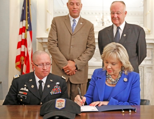 U.S Army Lt. Col. Jim Hill, left, joins Gov. Mary Fallin, Commissioner of Public Safety Michael Thompson, standing left, and Corrections Director Joe M. Allbaugh to sign a memorandum of agreement expected to help with a correctional officer shortage, at the State Capitol in Oklahoma City, Tuesday Aug. 2 2016. The DOC joined the PaYS program which provides U.S. Army soldiers, recruits and members of the Reserve Officers' Training Corps a guaranteed interview with partner employers. (Steve Gooch/The Oklahoman via AP)