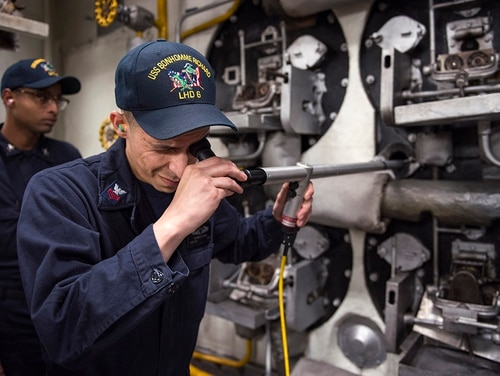 Machinist's Mate 1st Class Francisco Cejajimenez checks the interior of the No. 2 boiler onboard the amphibious assault ship Bonhomme Richard. Conventional surface machinist's mates with up to 10-years of service now qualify for re-enlistment bonuses. (MC2 Diana Quinlan/Navy)