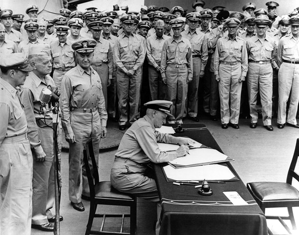 The surrender of Japan, Tokyo Bay, Sept. 2, 1945. Fleet Adm. Chester W. Nimitz signs the Instrument of Surrender as United States representative aboard USS Missouri (BB-63). Standing directly behind him are, left to right: Gen. Douglas MacArthur; Adm. William F. Halsey and Rear Adm. Forrest Sherman. (Navy)