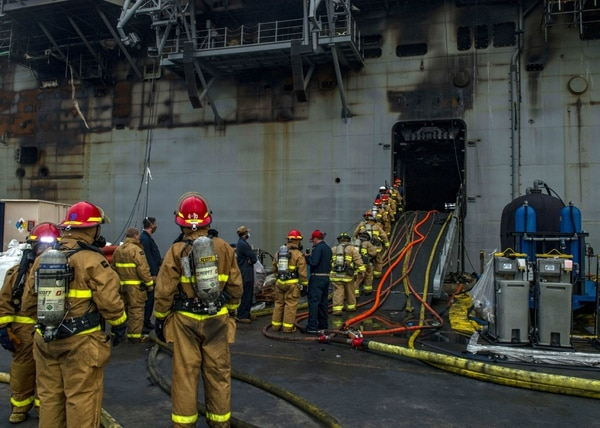 Sailors enter the amphibious assault ship Bonhomme Richard to fight the fires inside. (Navy)