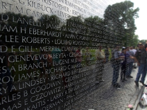 Visitors are reflected at Vietnam Veterans Memorial wall in Washington on May 27, 2018. Department of Veterans Affairs officials are opposing a plan to extend presumptive benefits status to tens of thousands of Vietnam veterans who served in ships off the coast of that country. (Jose Luis Magana/AP)
