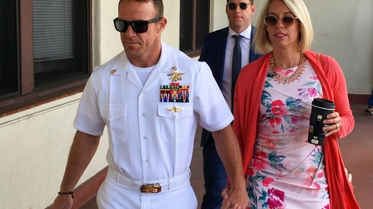 """Special Warfare Operator Chief Edward """"Eddie"""" Gallagher, left, walks with his wife Andrea to the Naval Base San Diego courthouse last year. (Julie Watson/AP)"""