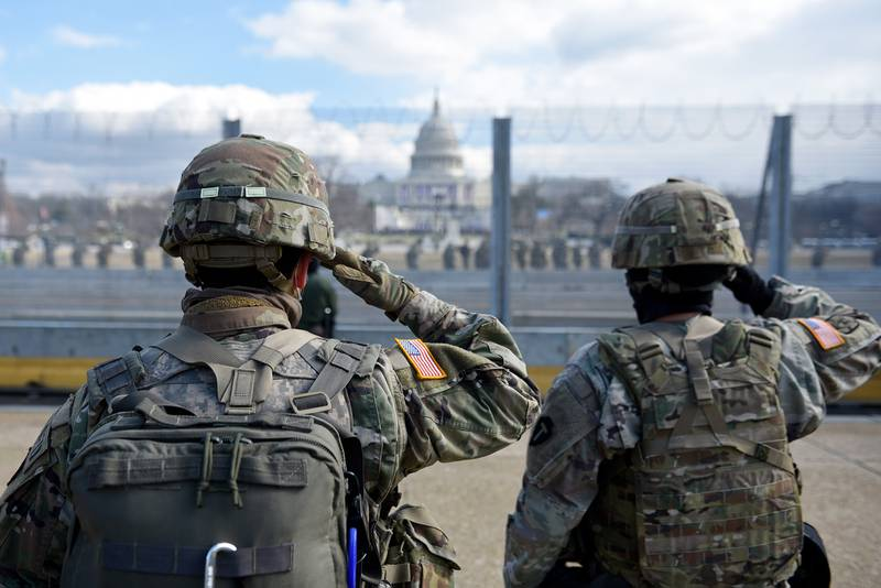 Members of the National Guard salute as they stand near the U.S. Capitol while the national anthem is sung during the inauguration of President-elect Joe Biden and Vice President-elect Kamala Harris on Jan. 20, 2021, in Washington.