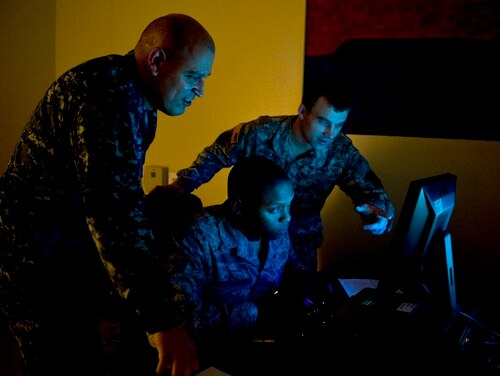 Officers from multiple branches analyze a scenario during Cyber Flag, an exercise that strategically focused on exercising the command's mission of operating and defending the Department of Defense networks across the full spectrum of operations against a realistic adversary in a virtual environment. (Senior Airman Matthew Lancaster/Air Force)
