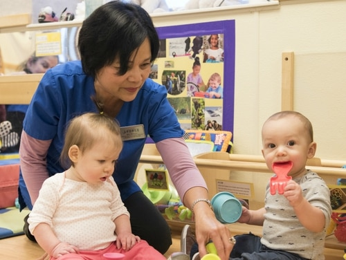Nelia McKeown, a Sitka Child Development Center child and youth program assistant, gives children toys to play with during playtime at Joint Base Elmendorf-Richardson, Alaska, Dec. 14, 2018. Service officials told lawmakers this week that daycare availability on military bases directly effects troops' readiness. (Airman 1st Class Crystal A. Jenkins/Air Force)