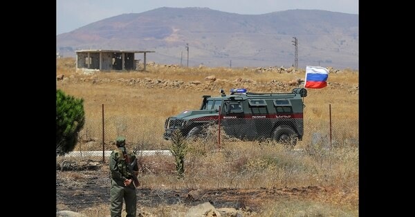 Syrian army soldier stands guard as Russian military police vehicle passes by near the town of Alhureyeh, Syria, Tuesday, Aug. 14, 2018. (Sergei Grits/AP)