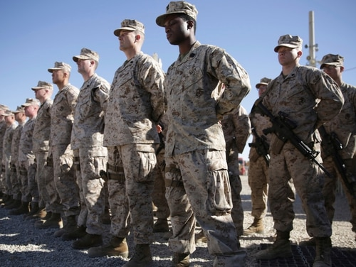 U.S. Marines stand guard during a ceremony in Helmand province, Afghanistan, in January. The Pentagon is developing plans to withdraw up to half of the 14,000 American troops serving in Afghanistan, U.S. officials said Thursday, Dec. 20, 2018, marking a sharp change in the Trump administration's policy aimed at forcing the Taliban to the peace table after more than 17 years of war. (Massoud Hossaini/AP)