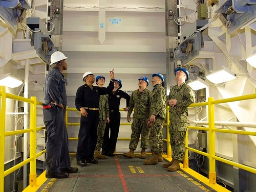 Sailors from the aircraft carrier Gerald R. Ford's weapons department meet the new weapons elevator. (Mass Communication Specialist 1st Class Jeff Troutman/Navy)