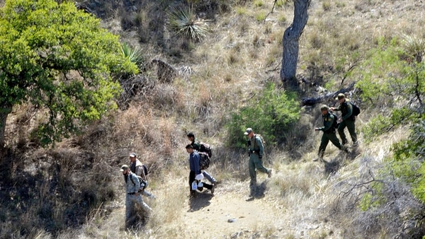 U.S. Border Patrol agents escort four undocumented immigrants captured near the U.S.-Mexico border on April 23, 2015. A Mississippi Army National Guard LUH-72 Lakota helicopter helped locate the men beneath a tree along a mountainside near Nogales, Ariz. (Staff Sgt. Scott Tynes/Mississippi Army National Guard)