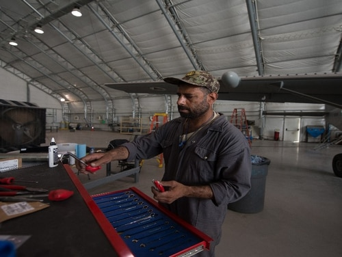 An Afghan Air Force C-208 maintainer sorts tools during maintenance of the aircraft Aug. 8 at Kabul Air Wing, Afghanistan. (Staff Sgt. Alexander W. Riedel/ Air Force)