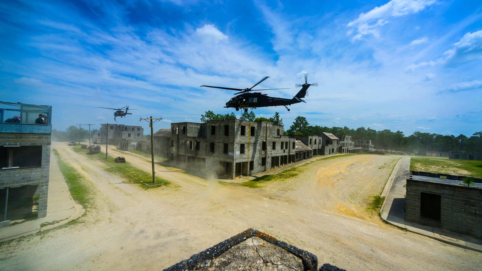 Black Hawks from the 160th Special Operations Aviation Regiment hover while Army Rangers prepare to fast rope onto buildings during a June 6 exercise at Fort Bragg, N.C. (Michael Bottoms/SOCOM)