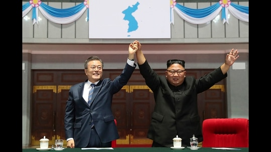 South Korean President Moon Jae-in and North Korean leader Kim Jong Un raise their hands after watching the mass games performance of