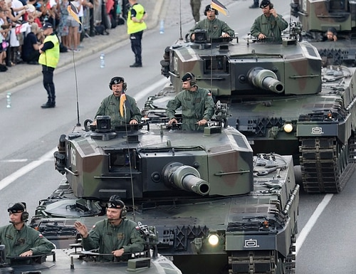 Tanks roll on one of the city's main streets during a yearly military parade celebrating the Polish Army Day in Warsaw, Poland, Wednesday, Aug. 15, 2018. Poland marks Army Day with a parade and a call for US permanent military base in Poland. (AP Photo/Alik Keplicz)