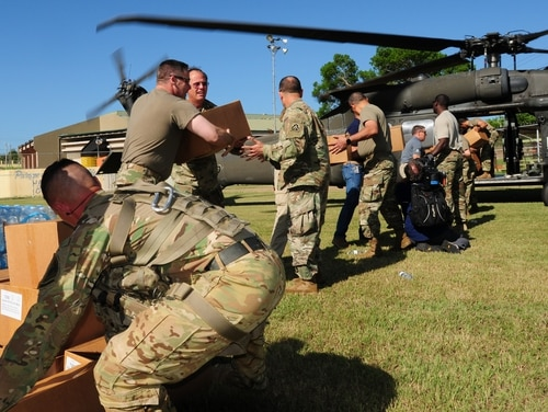 Brig. Gen. Jose Reyes, the dual status commander for Joint Task Force Puerto Rico, alongside other National Guard members, participates in the offloading of Meals Ready to Eat (MREs) in Barranquitas, Puerto Rico, Oct. 24, 2017. (Army)