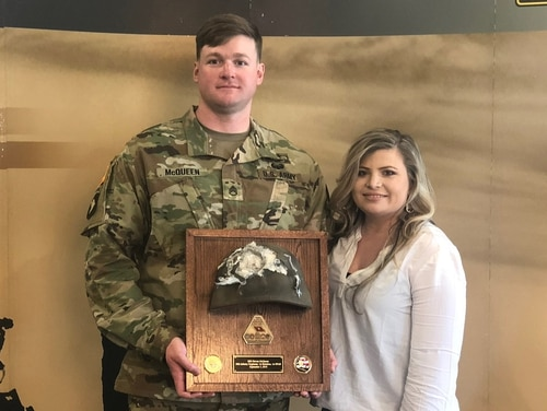 Staff Sgt. Bryan McQueen and his wife Aaron McQueen stand with the Enhanced Combat Helmet he was wearing when he was shot in the head during an insider attack in Afghanistan on Sept. 3, 2018. (PEO Soldier)
