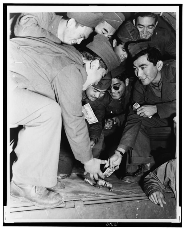 Killing time while the rest of their convoy loads, Japanese-American members of the 442nd Regimental Combat Team indulge in a little of the great American game of galloping dominoes with the bed of a GI truck as their table. (mid-1943 photograph from Camp Shelby, Mississippi, now in the collections of the Library of Congress).