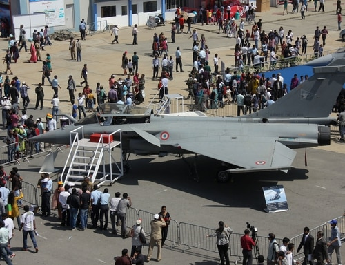Visitors look at the Dassault Rafale fighter aircraft on the fifth and final day of Aero India 2013 at Yelahanka Air Force station in Bangalore on February 10, 2013. Indian Air Force chief Marshal Birender Singh Dhanoa recently defended the decision of India's ruling National Democratic Alliance to buy 36 Rafale fighters from France. (Photo credit should read STR/AFP/Getty Images)