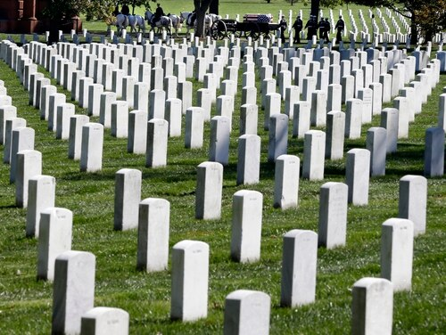 FILE - In this Oct. 22, 2012 file photo, a funeral procession passes behind rows of graves at Arlington National Cemetery in Arlington, Va. The Senate has passed legislation to allow female World War II pilots known as WASPs to continue placing their ashes at Arlington National Cemetery. (AP Photo/Jacquelyn Martin, File)