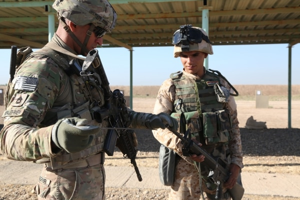U.S. Army Sgt. 1st Class Rapherson Morales-Rivera, a paratrooper assigned to Alpha Troop, 5th Squadron, 73rd Cavalry Regiment, 3rd Brigade Combat Team, 82nd Airborne Division, clears an Iraqi soldier's weapon at a rifle range at Camp Taji, Iraq, June 21, 2015. Iraqi soldiers from the 73rd Brigade, 16th Division trained with U.S. forces on rifle marksmanship as part of Combined Joint Task Force – Operation Inherent Resolve's multinational effort to defeat the Islamic State of Iraq and the Levant. (U.S. Army photo by Spc. Paris Maxey, CJTF-OIR Public Affairs)