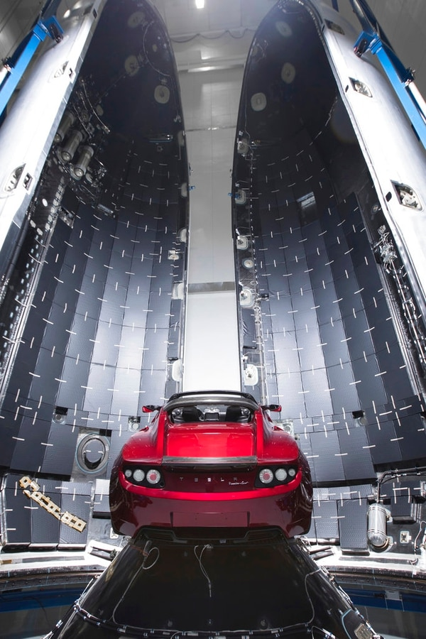 This Dec. 6, 2017, photo made available by SpaceX shows a Tesla car next to the fairing of a Falcon Heavy rocket in Cape Canaveral, Fla. For the Heavy's inaugural flight, the rocket will carry up Elon Musk's roadster. In addition to SpaceX, Musk runs the electric car maker Tesla. (SpaceX via AP)