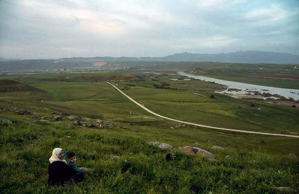 In this file photo dated May 1, 2019, a woman and child sit on a hill overlooking the Euphrates River as families picnic on May Day, in Derik, Syria. (Baderkhan Ahmad/AP)