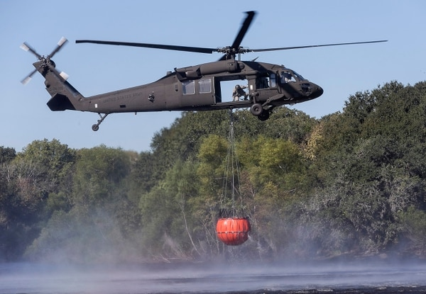 A Texas National Guard helicopters uses a bucket to pull water from the Buescher State Park Lake to drop on the Hidden Pines Fire near Smithville, Texas, Wednesday, Oct. 14, 2015. The Texas A&M Forest Service says challenging topography and uncontrolled fire lines has slashed the containment of the Bastrop County fire to 10 percent as night fell Wednesday. The Forest Service had estimated 50 percent containment earlier Wednesday. (Rodolfo Gonzalez/Austin American-Statesman via AP) AUSTIN CHRONICLE OUT, COMMUNITY IMPACT OUT, INTERNET AND TV MUST CREDIT PHOTOGRAPHER AND STATESMAN.COM, MAGS OUT; MANDATORY CREDIT